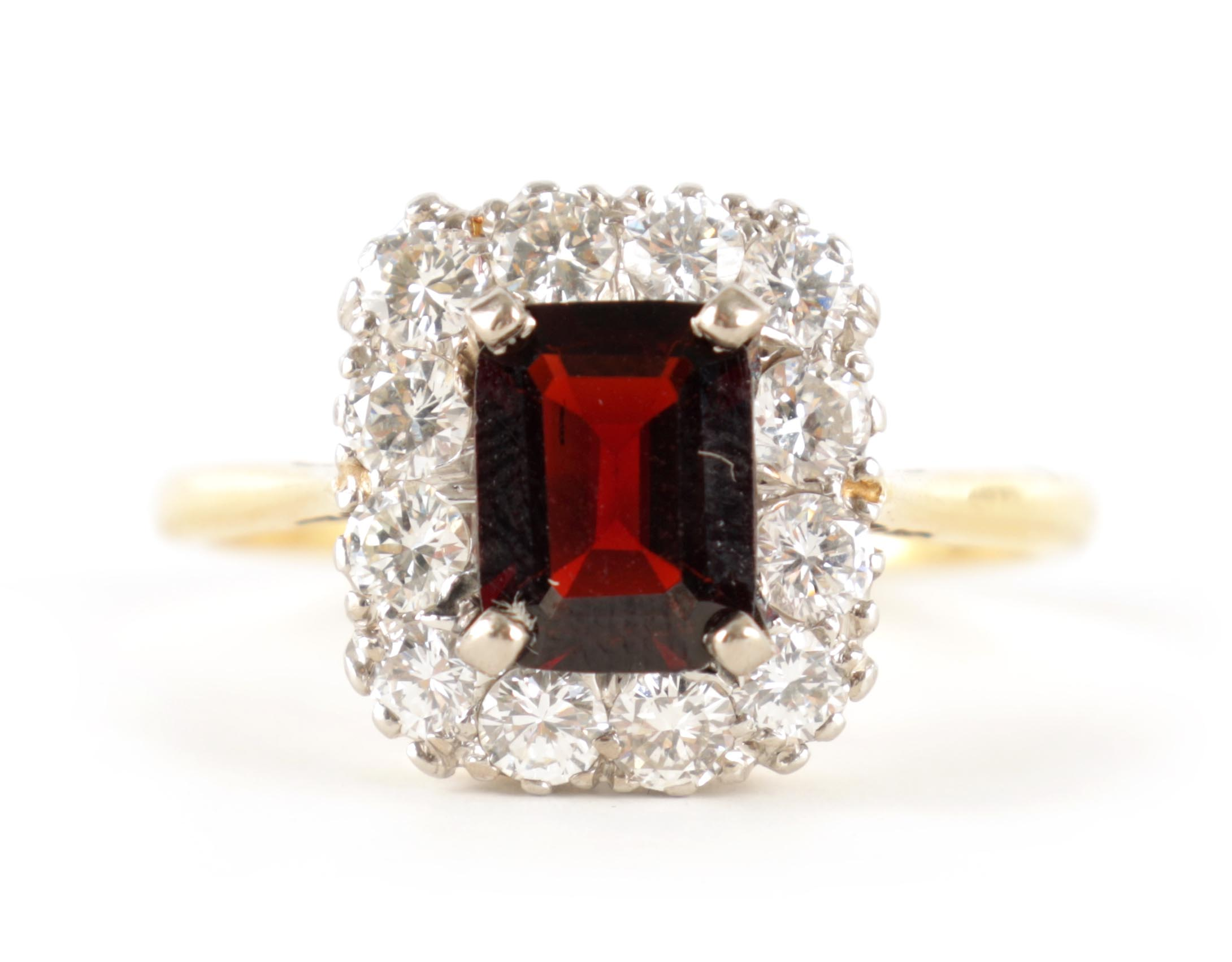A LADIES 18CT GOLD AND PLATINUM RUBY AND DIAMOND RING with emerald cut ruby surrounded by 12
