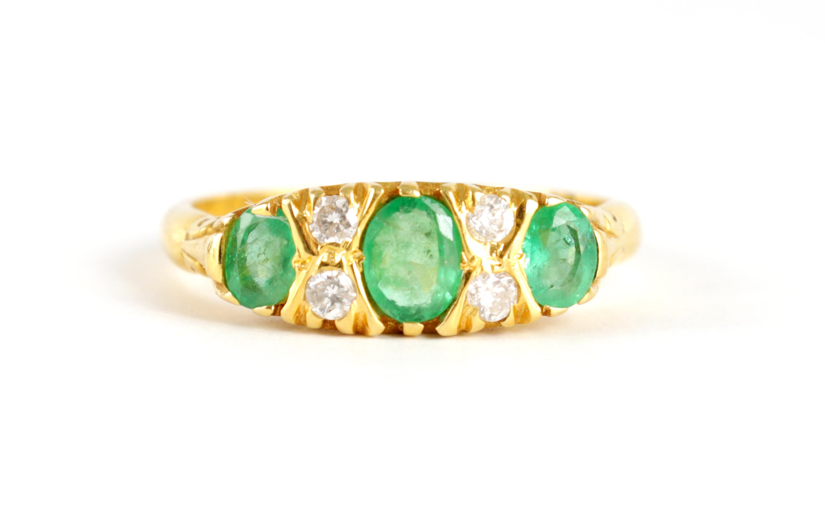 A LADIES 18CT GOLD DIAMOND AND EMERALD RING having four small diamonds set between three oval