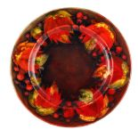 A 1930S MOORCROFT AUTUMN LEAF AND BERRY PATTERN FLAMBE PLATE 24cm diameter, impressed signature mark
