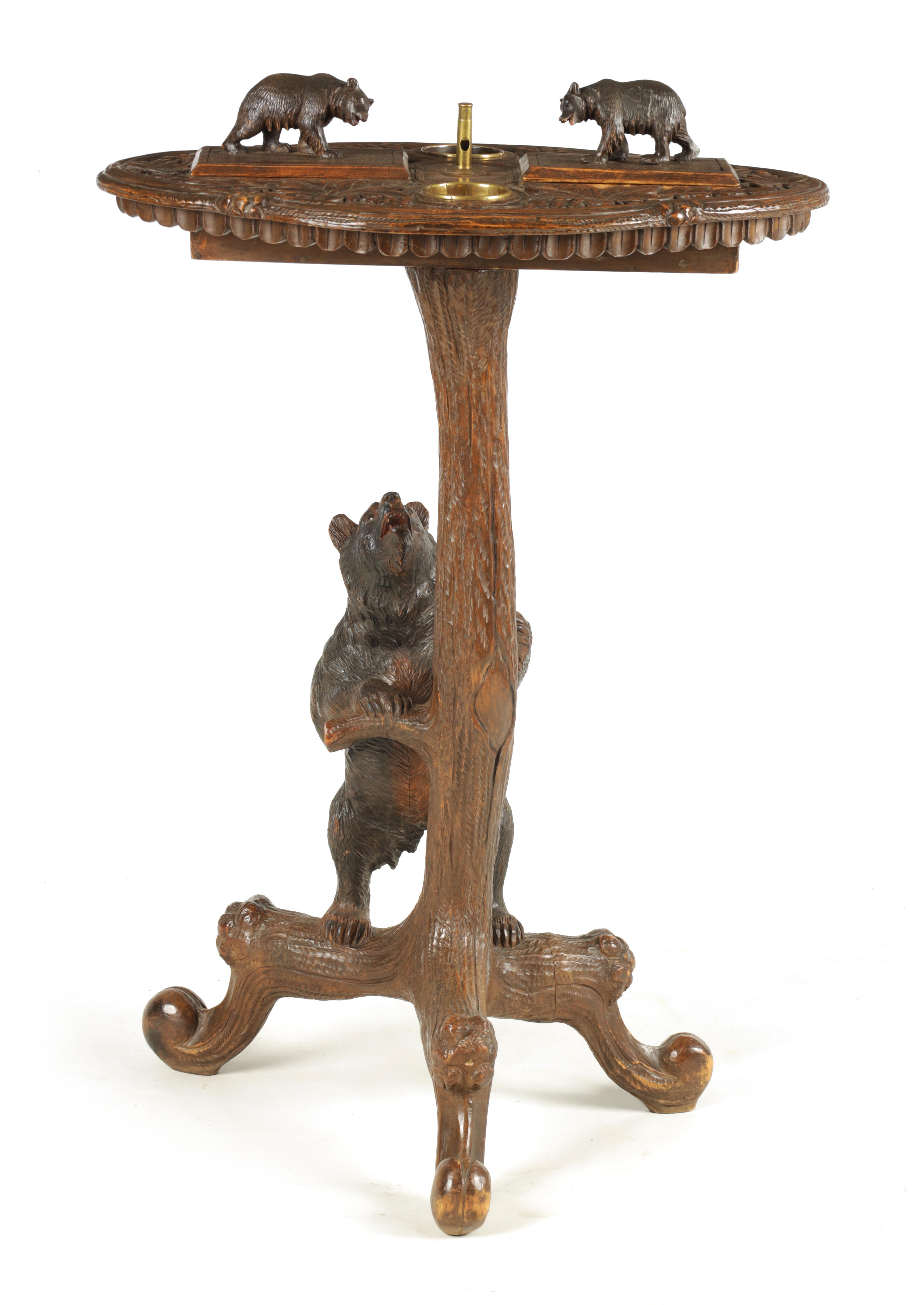 A LATE 19TH CENTURY SWISS CARVED BLACK FOREST SMOKERS TABLE with leaf carved top having two bear