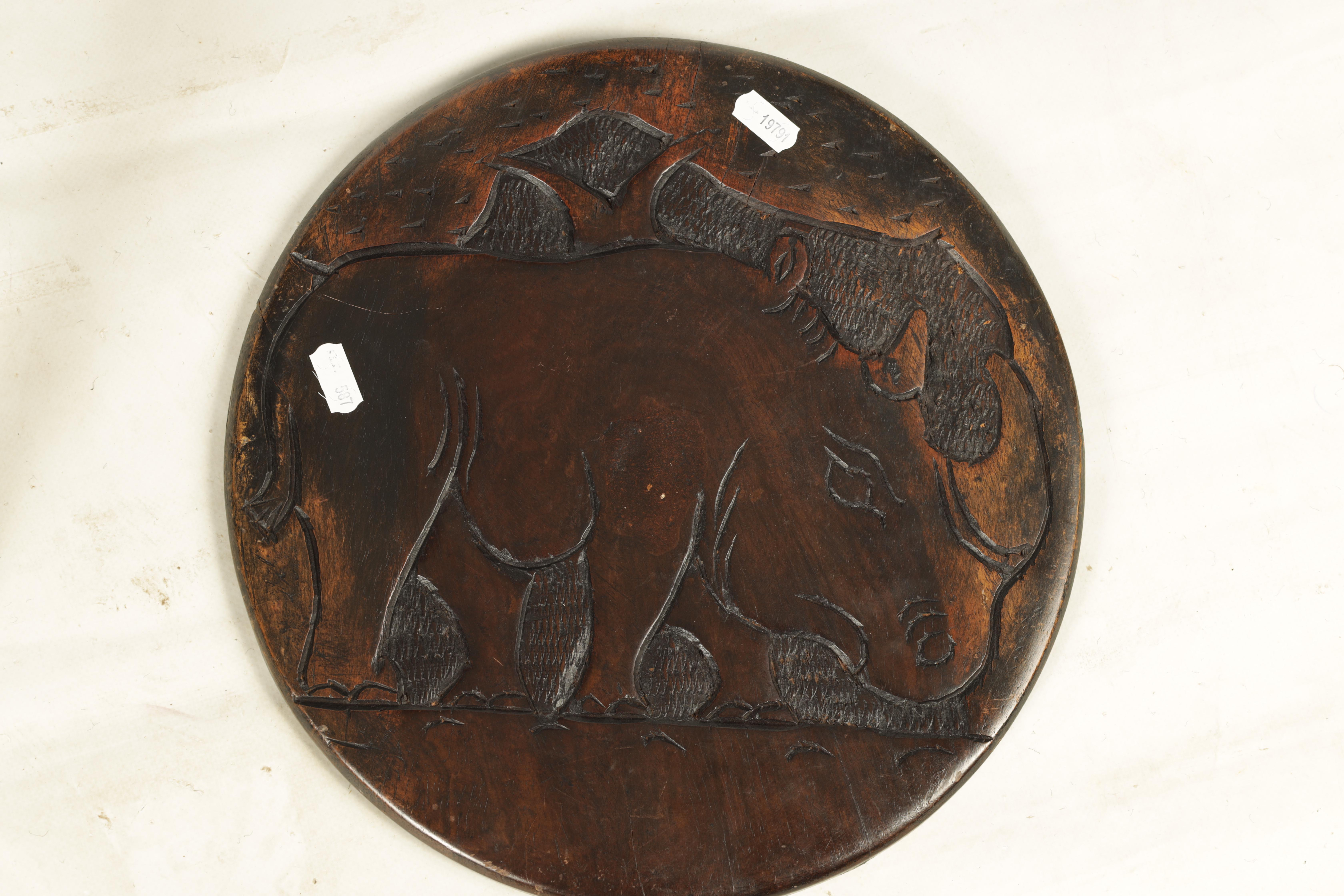 A LATE 19TH CENTURY AFRICAN HARDWOOD FOLDING TABLE the circular top relief carved with Rhinosorus - Image 4 of 7