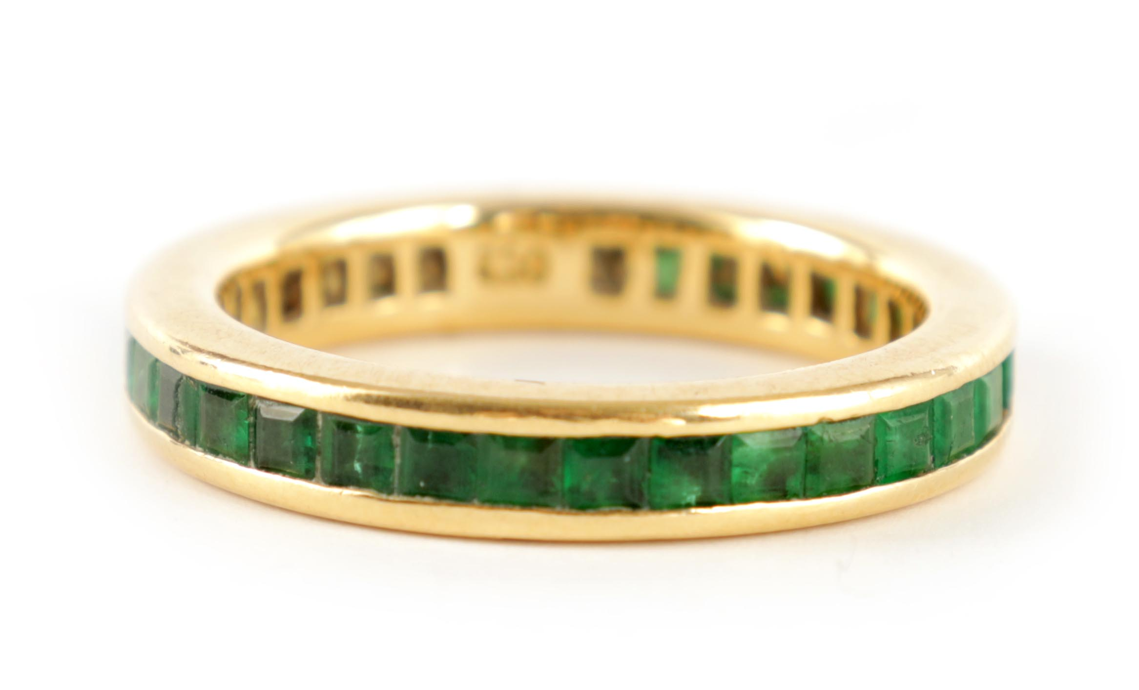 AN 18CT GOLD AND EMERALD ETERNITY RING set all round with square-cut stones, app. weight 4.5g