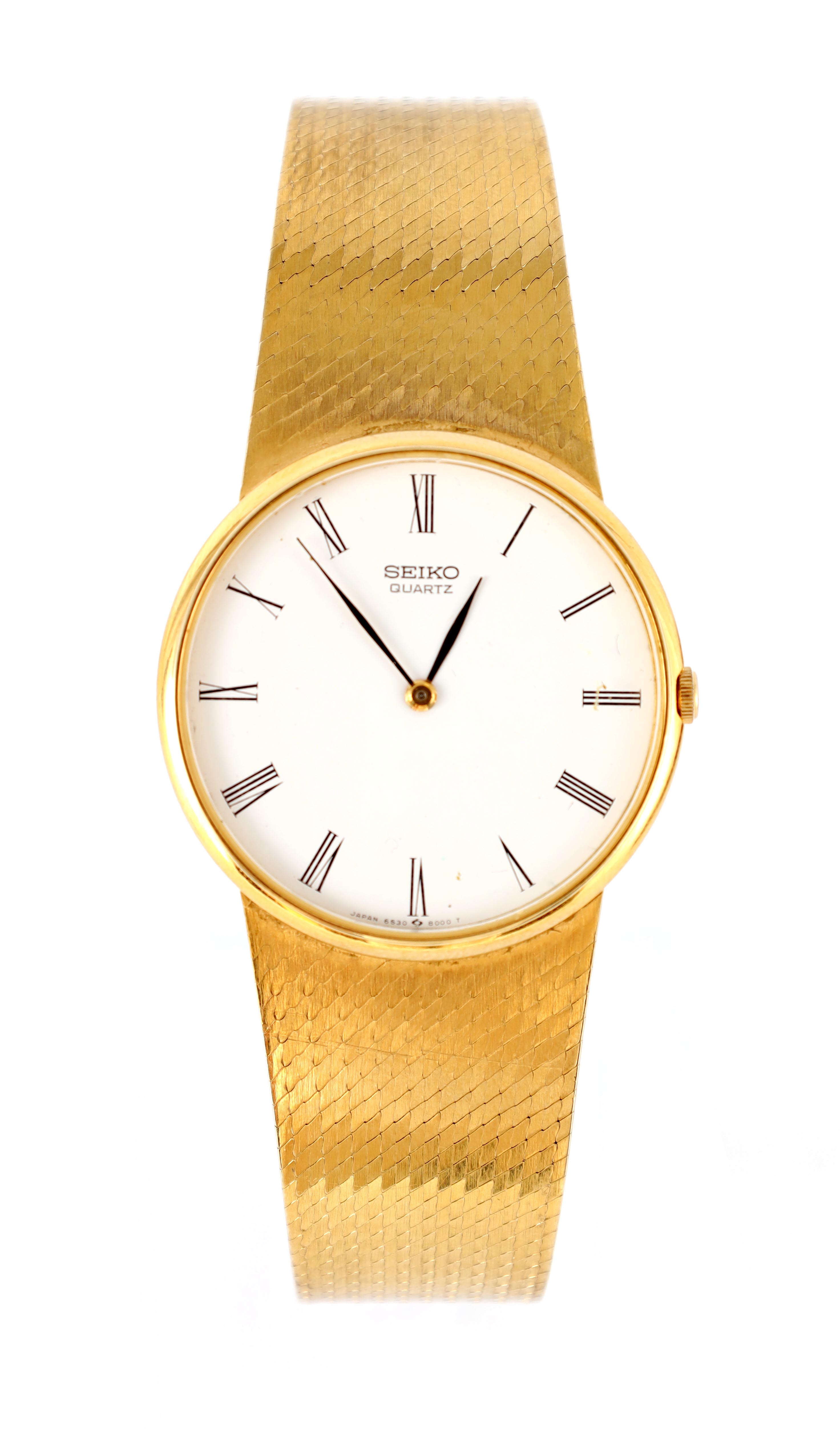 A GENTLEMAN'S 9CT GOLD SEIKO WRISTWATCH on original 9ct gold bracelet The white enamel dial with
