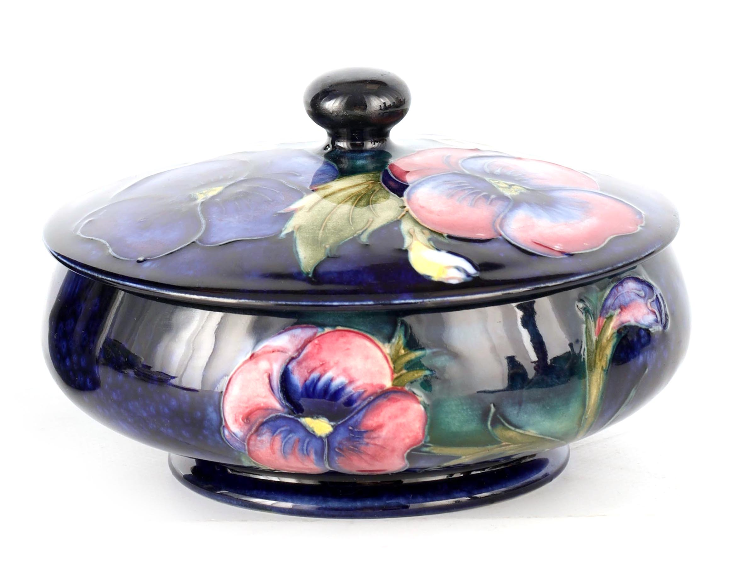 A MOORCROFT SHALLOW FOOTED BOWL AND COVER tube lined and decorated with leafing Pansy sprays on a