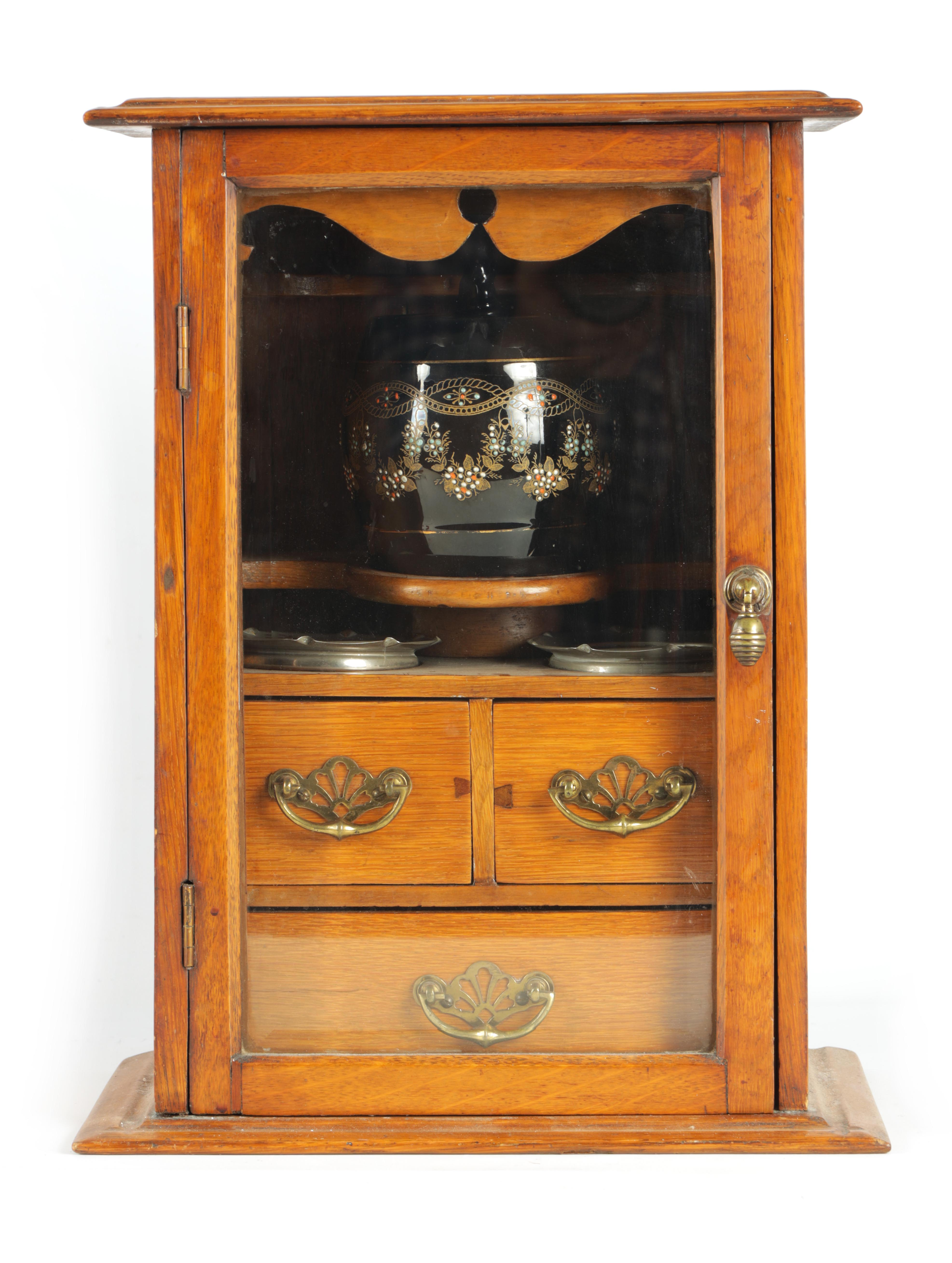 A STYLISH EDWARDIAN OAK SMOKERS CABINET with glazed door enclosing a shelved three drawer interior