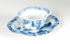 AN 18TH CENTURY CHINESE KANGXI BLUE AND WHITE SHAPED CUP AND SAUCER