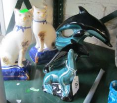 Two Poole Pottery dolphins (one a/f), a Poole Pottery seal and two Staffordshire cats (one a/f)