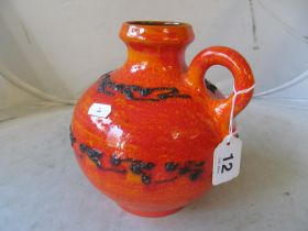 A West German pottery single handled jug with orange and red mottle ground and black lava style