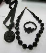 A Victorian jet carved rose design hair locket, black bead necklace and a bracelet