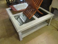 A large limed wood coffee table with glass inset top