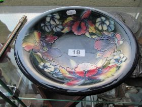 A Moorcroft dark blue glazed bowl decorated pink and blue flowers