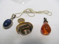 A gold coloured fob, amber style pendant and silver pendant with blue stone