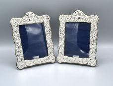 A Pair of London Silver Photograph Frames of Embossed Form, 19 x 14 cms