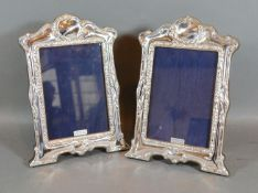 A Pair of Sterling Silver Photograph Frames, each of shaped and embossed form 21.5cm by 15cm