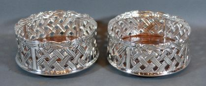 A Pair of Silver Plated and Turned Wooden Bottle Coasters of pierced form 12cm diameter