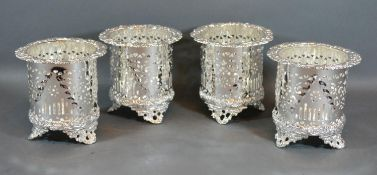 A Set of Four Silver Plated Bottle Stands of pieced embossed form upon shaped feet 12cm tall