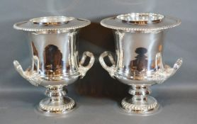 A Pair of Silver Plated Two Handled Wine Coolers with inner liners upon circular pedestal bases 27cm