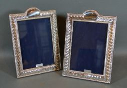 A Pair of Sterling Silver rectangular Photograph Frames with embossed decoration 20cm by 13.5cm