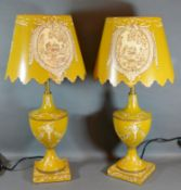 A Pair of Tollware Table Lamps and Shades with painted decoration upon a yellow ground 55cm tall