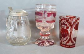 A Bohemian Ruby Glass Beaker together with a similar Goblet and a clear glass lidded Tankard