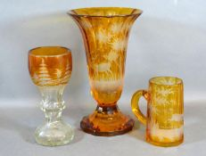 A Bohemian Amber Glass Vase with Flared Rim, the etched decoration in the form of a Stag within a