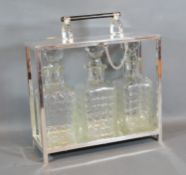 A Silver Plated Tantalus, the hinged top above three cut glass decanter with stoppers 28cm by 10cm