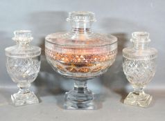 A Garniture of Three 19th Century Glass Covered Vases with square pedestal bases, 33 cms and 26