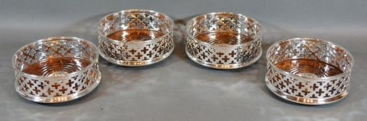 A Set of Four Silver Plated and Turned Wooden Bottle Coasters of pierced form 12.5cm diameter