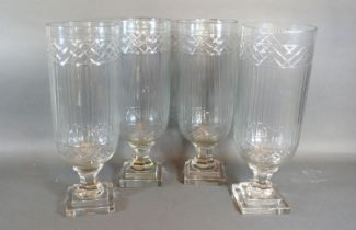 A Set of Four Glass Storm Lamps with square stepped bases, 34 cms tall