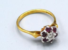 An 18ct. Gold Ruby and Diamond Cluster Ring with a central diamond surrounded by rubies, claw set,