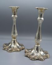 A Pair of Silver Plated Candlesticks of shaped fluted design with outswept foot and decorated with
