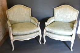 A Pair of French Painted Fauteuils each with a padded back and seat with scroll arms raised upon