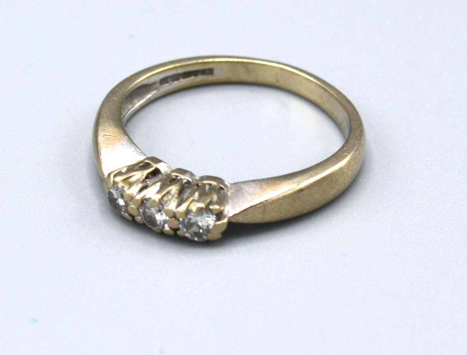 An 18ct White Gold Three Stone Diamond Ring with pierced setting, 3.2 gms Size L