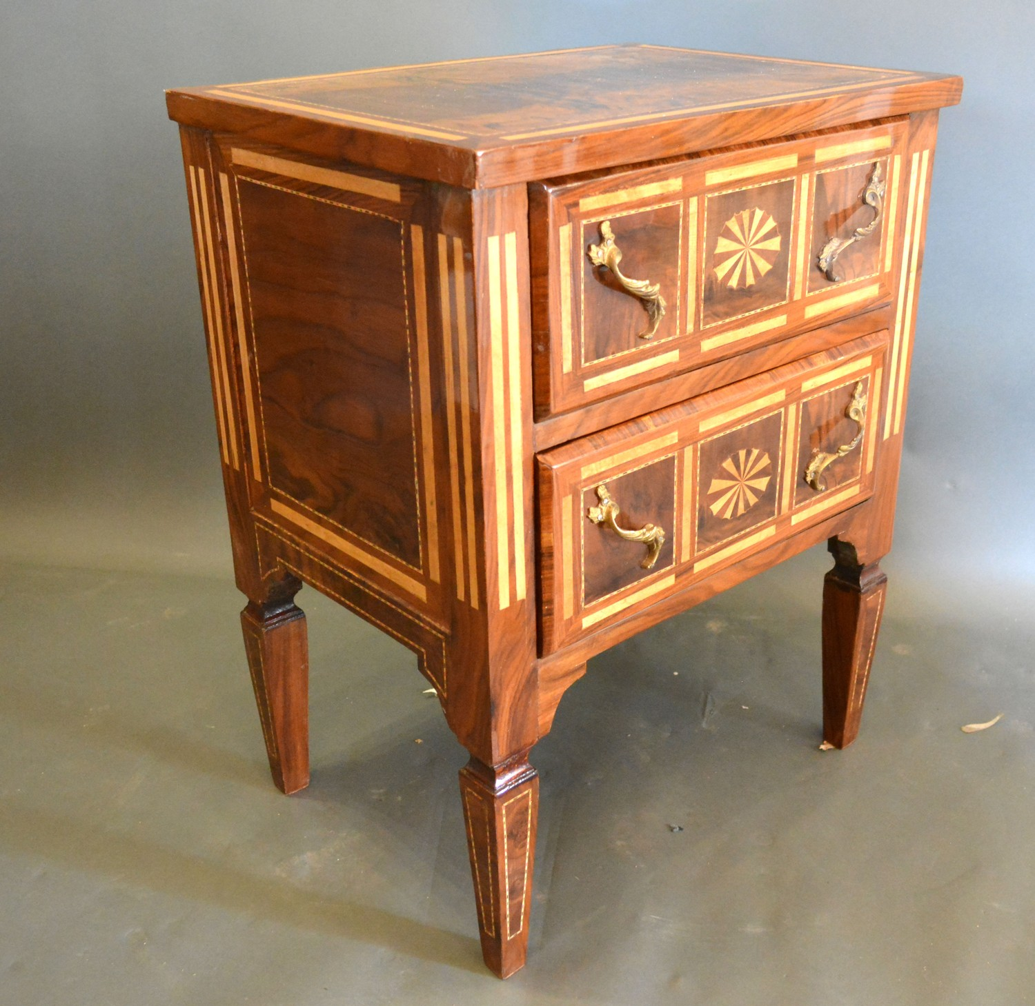 A French inlaid bedside chest, the inlaid top above two oval inlaid drawers with brass handles,