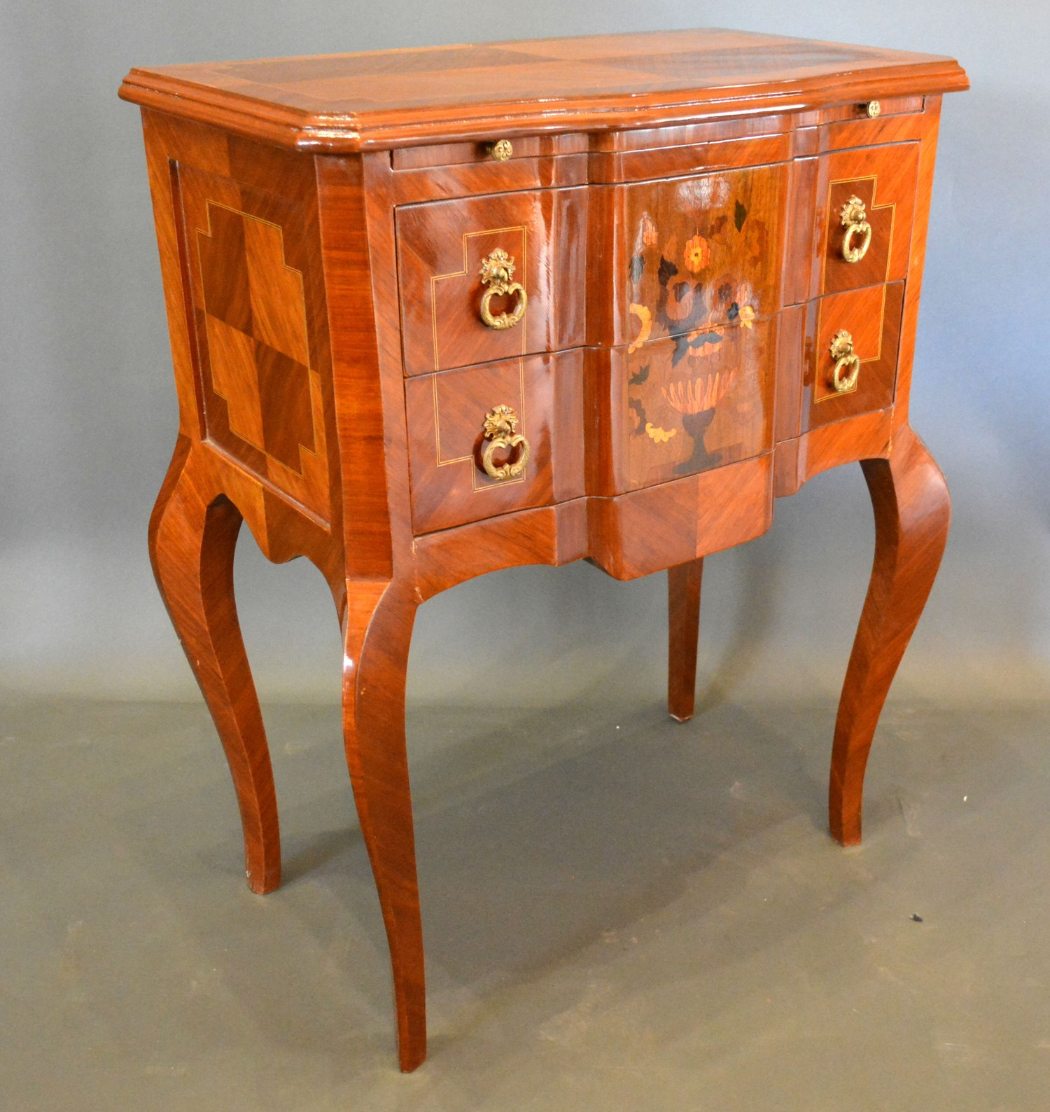 A French style chest, the inlaid shaped top above two marquetry inlaid drawers with brass drop