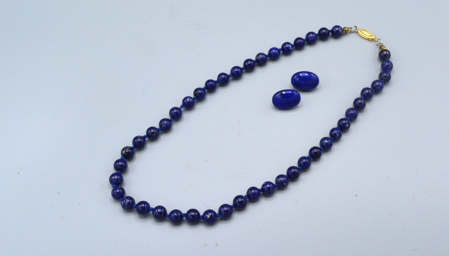 A blue stone bead necklace with 14ct gold clasp together with a similar pair of ear studs