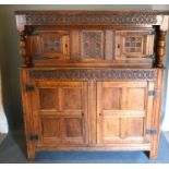 A George III Oak Court Cupboard with a carved frieze above a central carving flanked by doors, the
