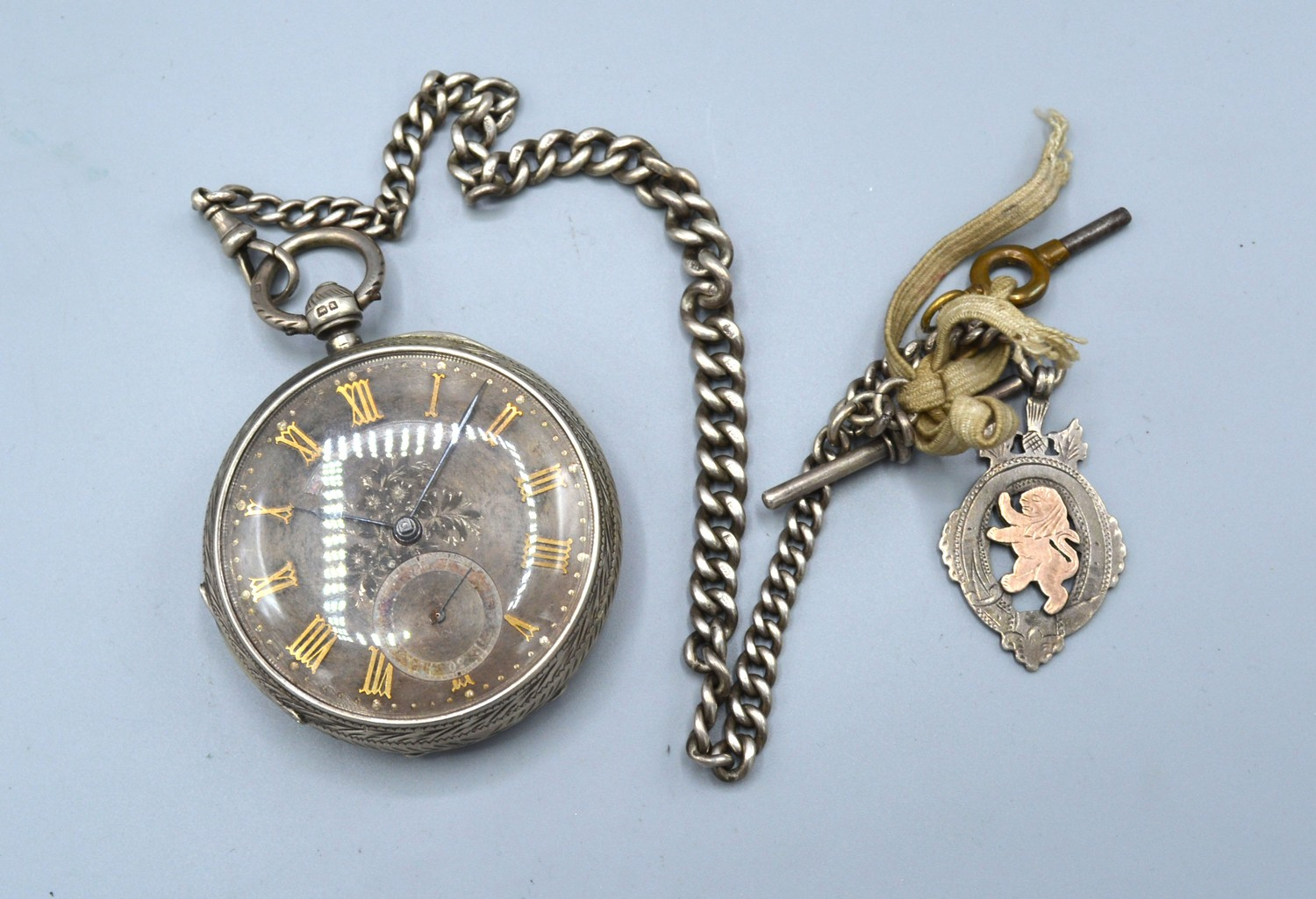 A Chester silver cased pocket watch, the engraved dial with gold mounts and with silver cur link