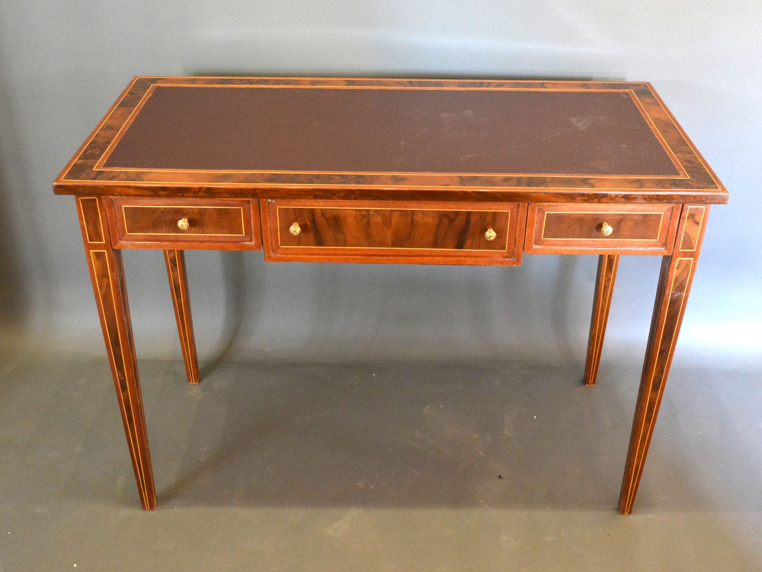 A French style writing desk, the leather inset top above three drawers with lion mask handles raised