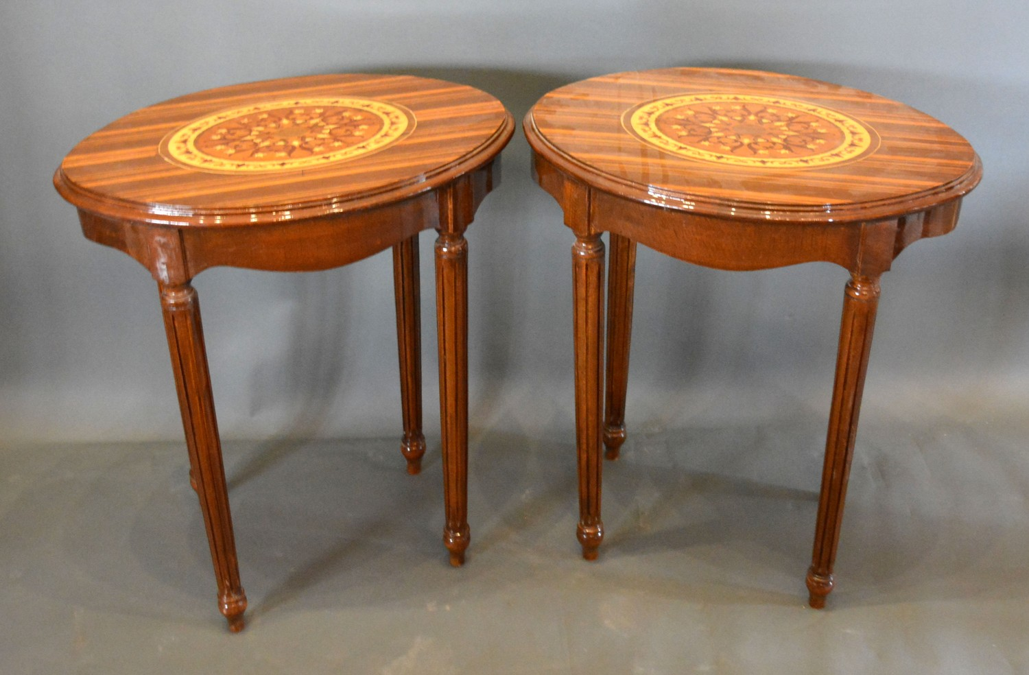 A Pair of French marquetry inlaid oval lamp tables each with an oval marquetry inlaid moulded top