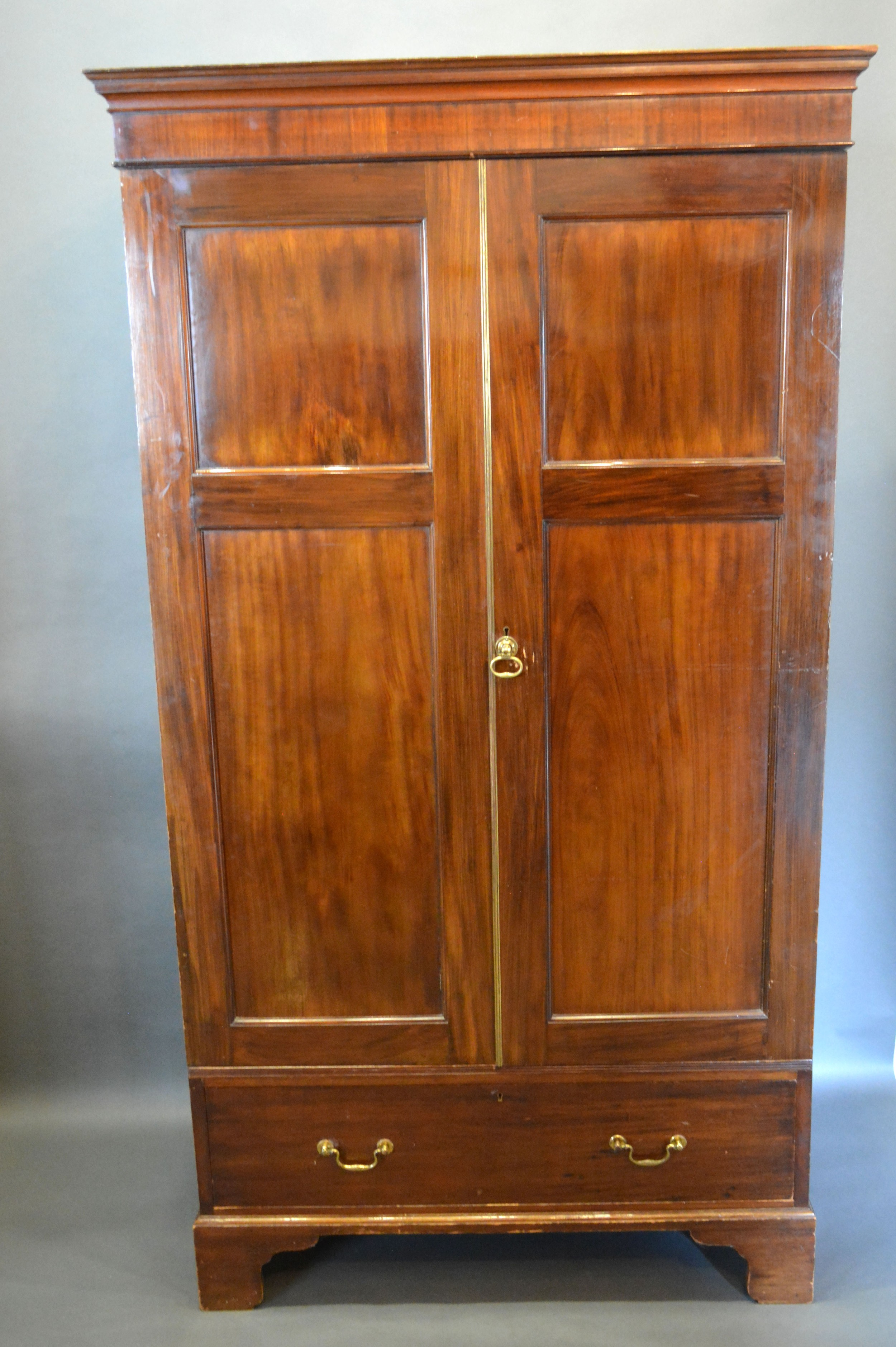 A late 19th century mahogany hall cupboard, the moulded cornice above two doors above drawer