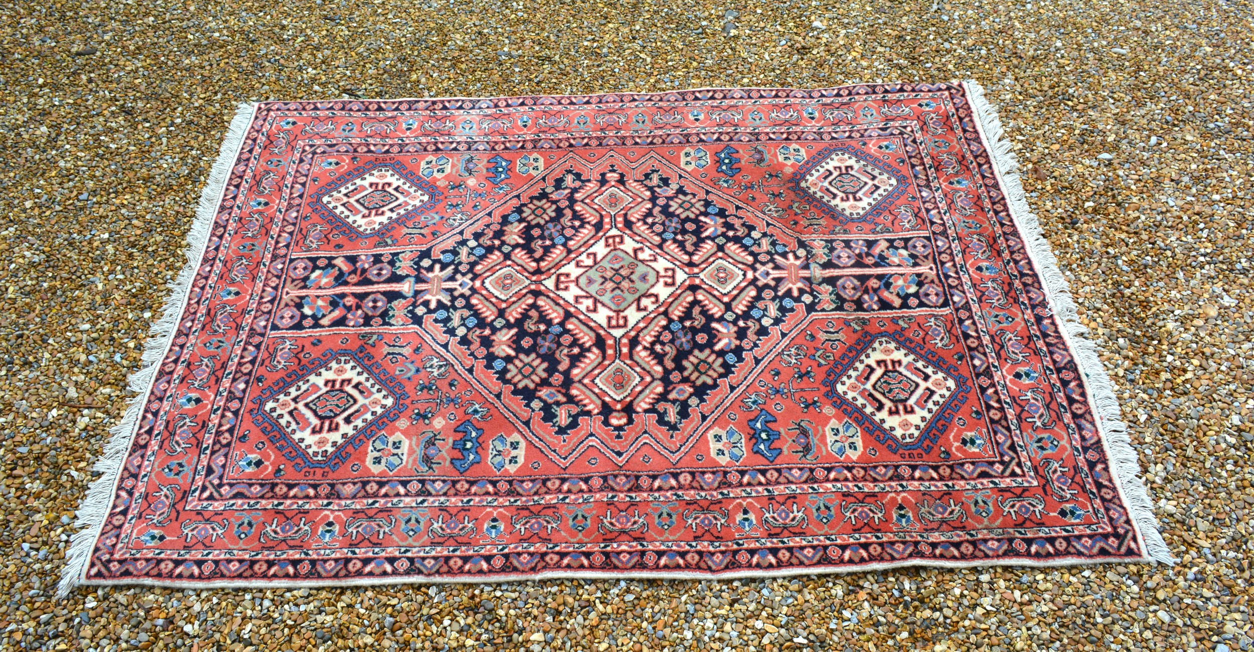 A North West Persian woollen rug with a central medallion within an all over design upon a red, blue