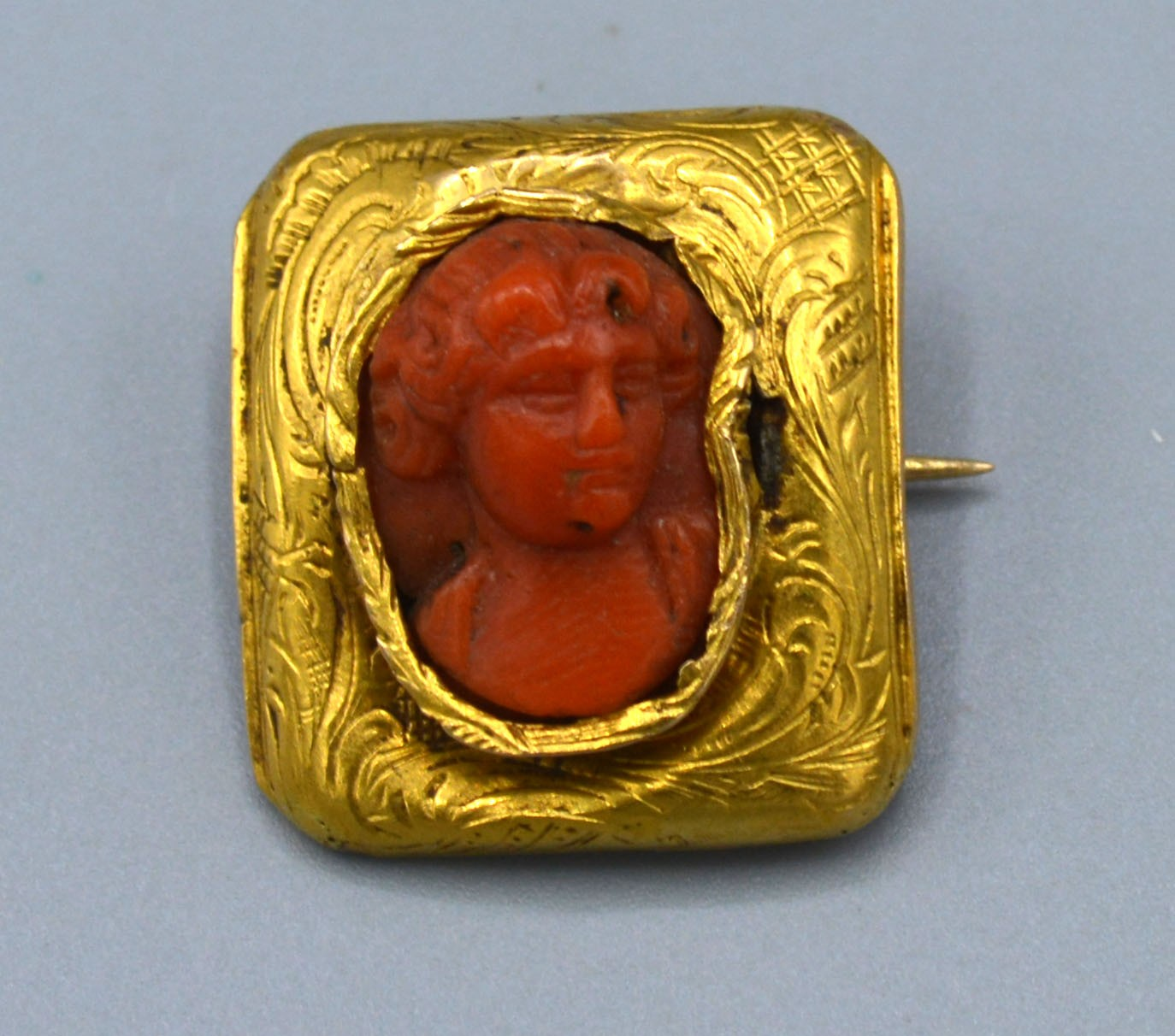 A Small Rectangular Brooch the carved coil centre in the form of a classical figure 2 x 1.5 cms