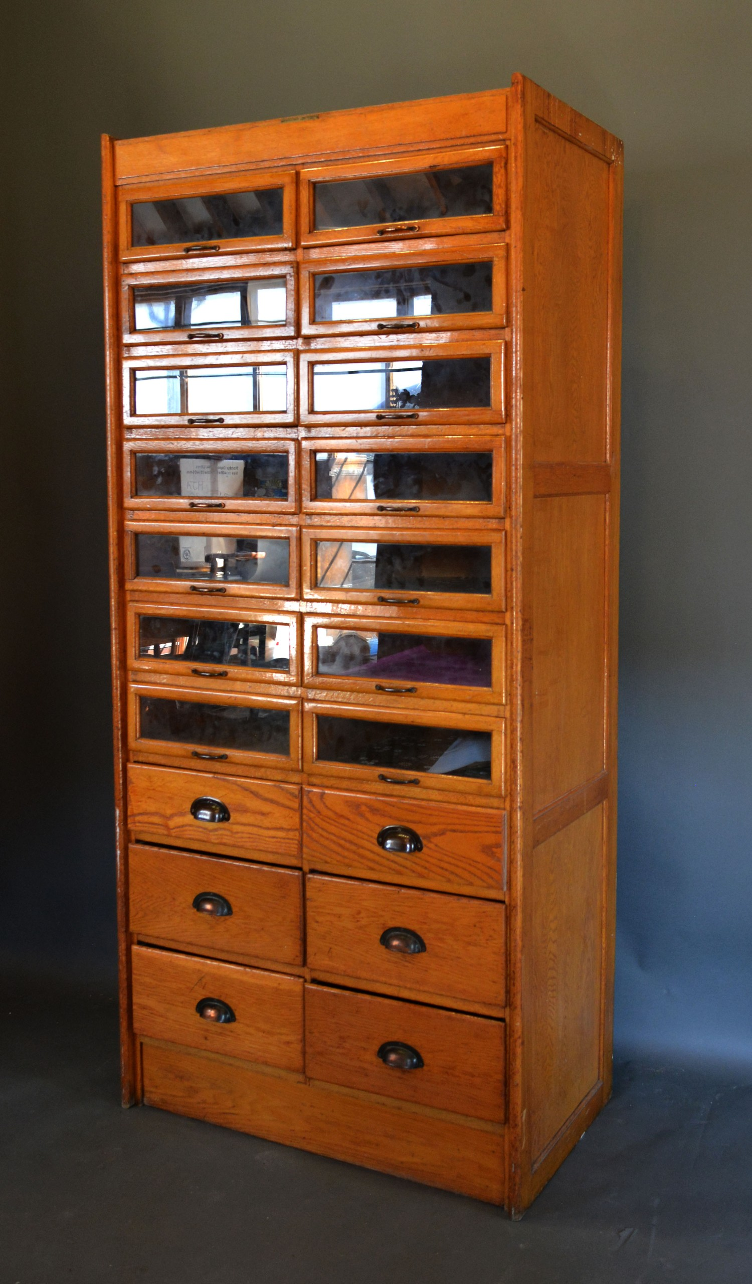 An early 20th century oak Haberdashery cabinet, with fourteen glazed drawers above six drawers