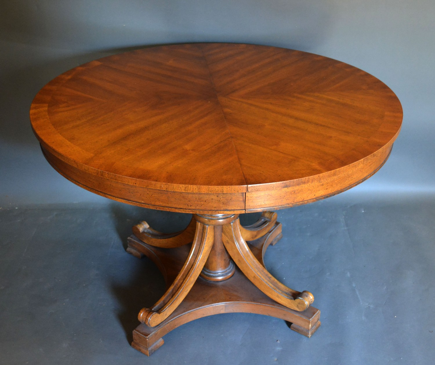 A 20th century circular centre table with turned centre column and outset legs, 113cms diameter,
