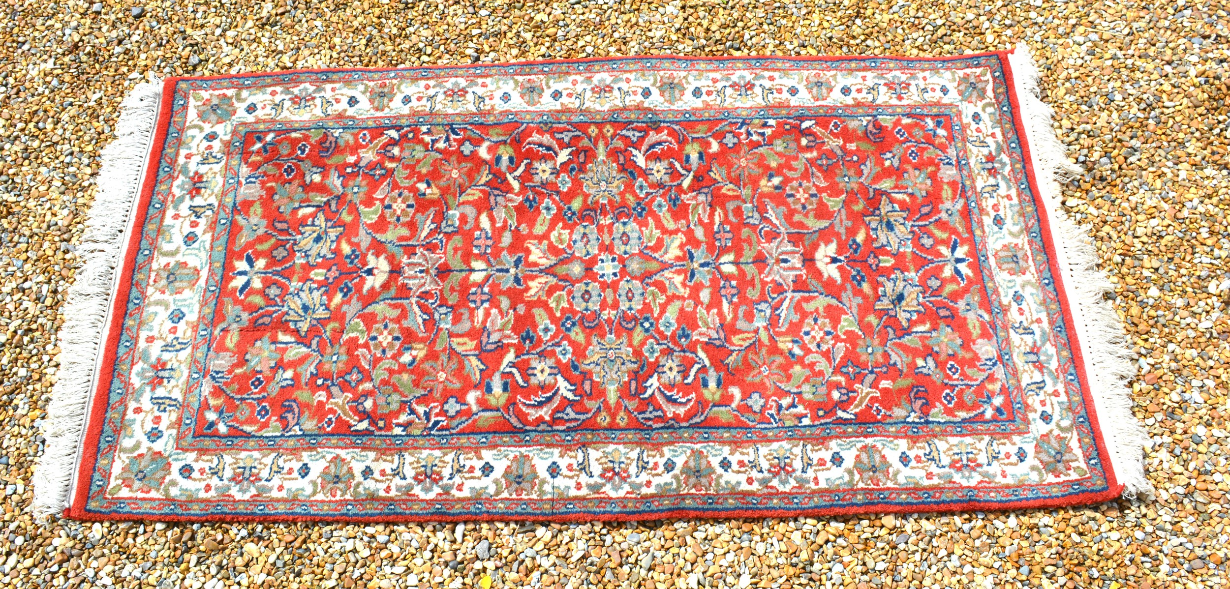 A North West Persian small rug with an all over design upon a red, blue and cream ground within