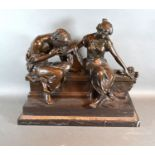A 20th century patinated bronze group in the form of two classical figures on a bench, bearing