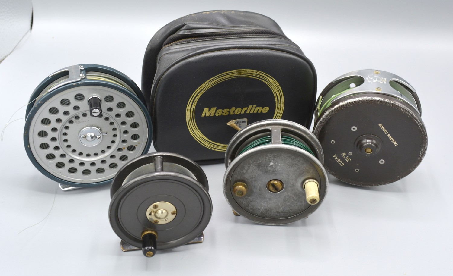 The Cobra fishing reel by Farlows London, 9cms diameter together with another reel by Masterline,
