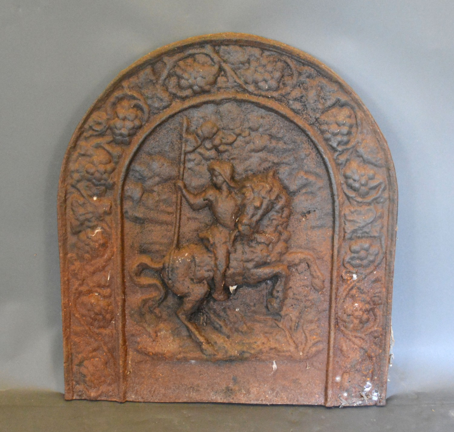 An early cast iron fire back of arched form, decorated in relief with a figure on horse back,