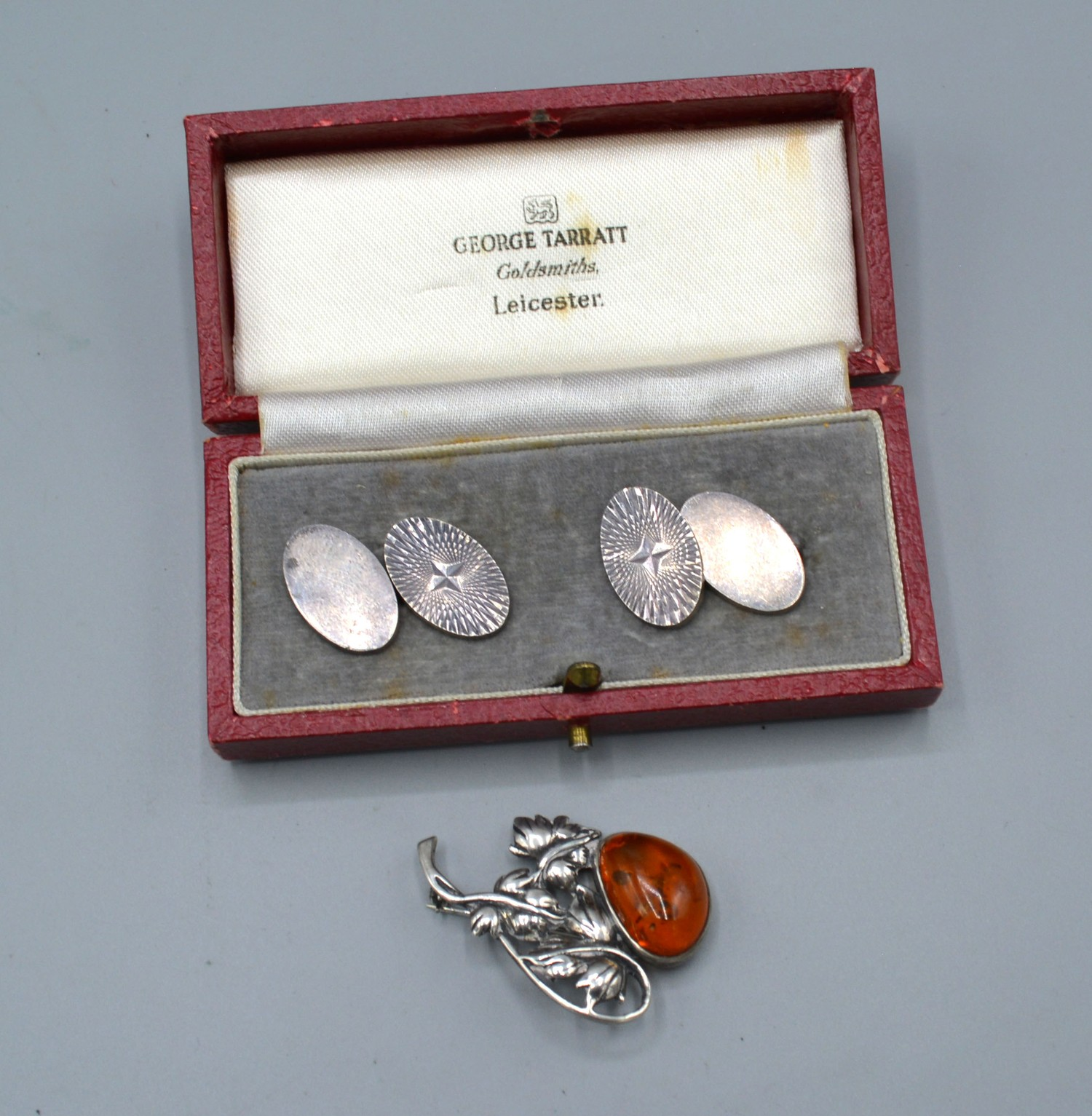 A silver brooch set amber together with a pair of silver cufflinks